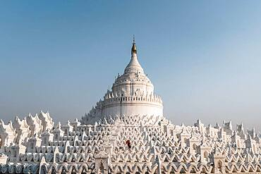 Buddhist monk stands with red umbrella in front of Hsinbyume Pagoda, Mingun, Myanmar, Asia
