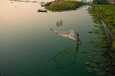 Fishermen on Taung Tha Man Lake throw out a fishing net for sunrise, reflection in the water, Thaung Tha Man Lake, Mandalay, Myanmar, Asia