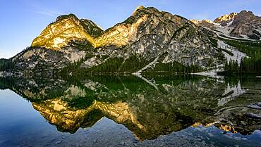 Mountains in the evening light are reflected in Lake Prags Lake, Lago di Lake Prags, Lake Prags Valley, Lake Prags, Dolomites, South Tyrol, Alto Adige, Italy, Europe