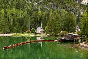 Chapel and boathouse with rowing boats at the Lake Prags Lake, Lago di Lake Prags, Lake Prags Valley, Lake Prags, Dolomites, South Tyrol, Alto Adige, Italy, Europe