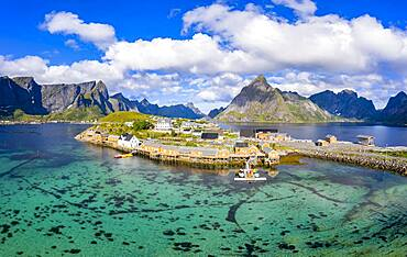 Rorbuer cabins by the fjord with Bergen in the background, fishing village Sakrisoy, Sakrisoy, Reine, Lofoten, Norway, Europe