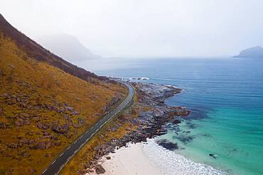 Drone shot, road between a mountain and in front of a fine sandy beach, Haukland beach, Lofoten, Norway, Europe