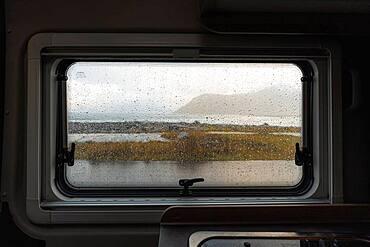View from rainy campervan kitchen window on Flakstad beach, Flakstad, Lofoten, Norway, Europe