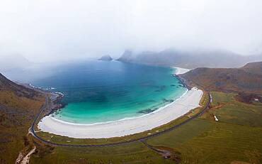 Drone shot, White sand beach with sea, mountains and orange grass, Haukland beach, Lofoten, Norway, Europe