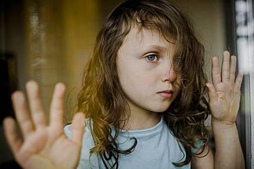 Child looks sadly through window pane