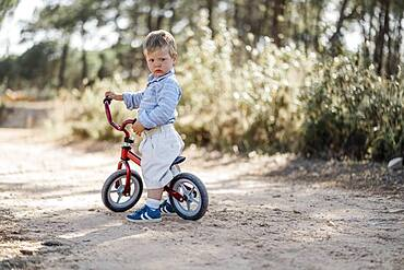Cute toddler riding his balance bicycle on a dirt road