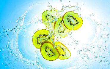Slices of the kiwi with water splashes, light blue background