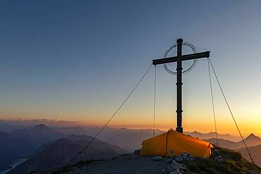 Sunset over Lechtal mountains, in the foreground summit cross of the Geierkopf with tent, Reutte, Ammergau Alps, Tyrol, Austria, Europe