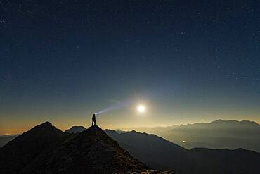 Mountaineer on summit ridge with full moon and starry sky, in the background Ammergau Alps, Reutte, Ammergau Alps, Tyrol, Austria, Europe
