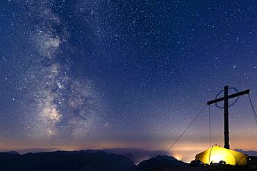 Night sky with stars and milky way over Lechtal mountains, in the foreground summit cross of the Geierkopf with tent, Reutte, Ammergau Alps, Tyrol, Austria, Europe