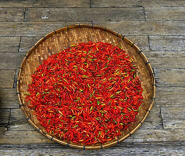 Drying red chillies in a bowl, Luang Prabang, Laos, Asia