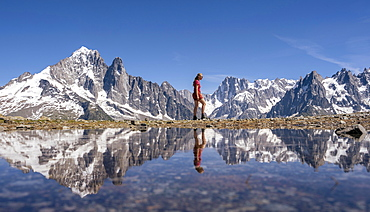 Young woman walking in front of mountain panorama, reflection in Lac Blanc, mountain peaks, Grandes Jorasses and Mont Blanc massif, Chamonix-Mont-Blanc, Haute-Savoie, France, Europe