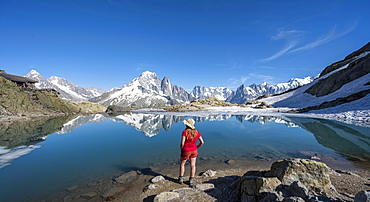Young woman in front of mountain panorama, reflection in Lac Blanc, mountain peaks, Grandes Jorasses and Mont Blanc massif, Chamonix-Mont-Blanc, Haute-Savoie, France, Europe