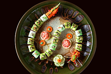 Sushi decorated in form of a dragon on round plate