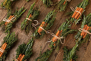Cinnamon sticks tied together with rosemary and thyme, several bunches of herbs next to each other, on wooden underground