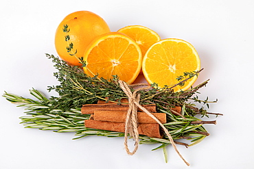 Fresh oranges with cinnamon sticks tied together with rosemary and thyme, white background