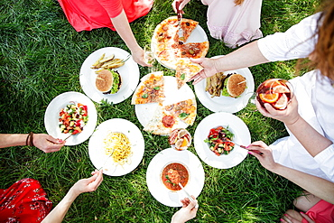 Group of women enjoying different food on grass, pizza, burger, salads, pasta, soup