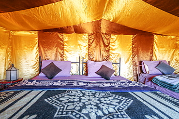 Three beds inside elegant tent set on Sahara desert, Morocco, Africa
