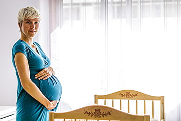 Pregnant woman holding her belly by baby cot next to the window
