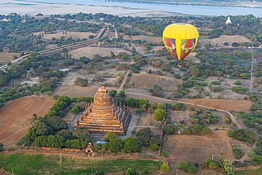 Hot air balloon at sunrise over a temple, Bagan, Myanmar, Asia