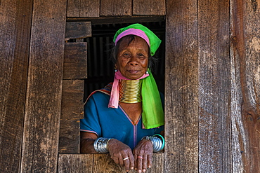 Padaung, giraffe, woman standing in a window frame of her house, Panpet, Loikaw area, Kayah state, Myanmar, Asia