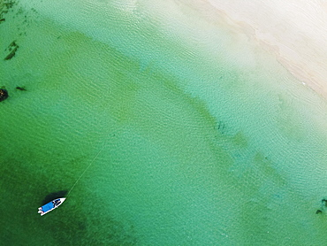 Aerial of a little boat in the clear waters anchoring on a beach on Smart island, Mergui or Myeik Archipelago, Myanmar, Asia