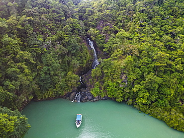 Aerial of a waterfall dropping right in the ocean on Dome island, Mergui or Myeik Archipelago, Myanmar, Asia