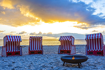 Beach chairs and fire bowl at sunrise at the big beach of Thiessow, island Ruegen, Baltic Sea, Mecklenburg-Western Pomerania, East Germany