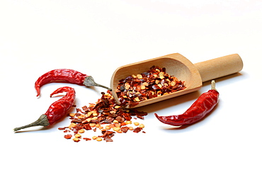 Chili flakes in wooden shovel and dried chili peppers, Germany, Europe