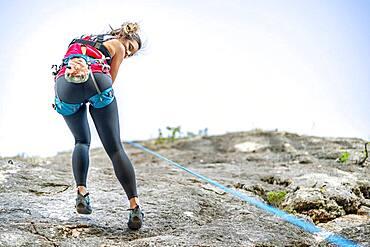 A woman climbing a steep rock using climbing harness