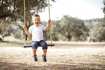 Cute happy blond toddler on the swing, Portugal, Europe