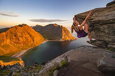 Evening atmosphere, Young woman bouldering, Climbing, Peak of Ryten, Sea, Kvalvika beach and mountains, Fredvang, Lofoten, Nordland, Norway, Europe
