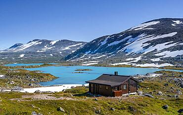 Turquoise lake and mountains, cabin on the Norwegian Landscape Route, Gamle Strynefjellsvegen, between Grotli and Videsaeter, Norway, Europe