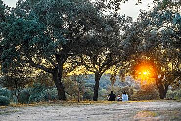 Family with a small kid enjoying the sunset in the nature