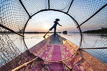 Fisherman at Inle Lake with traditional Intha conical net at sunset, fishing net, leg rowing style, Intha people, Inle lake, Shan state, Myanmar, Asia