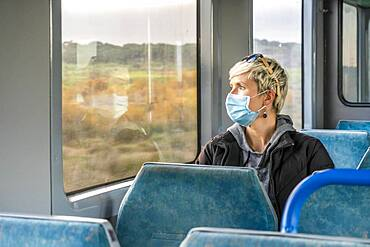 Serious woman wearing surgical mask looking through the window in a train, Portugal, Europe