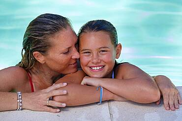 Woman with daughter at pool, in water, italy