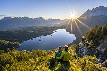 Two (hikers) looking at Eibsee lake at sunrise, sun shining over Bavarian alpine foothills, right Zugspitze, Wetterstein mountains near Grainau, Upper Bavaria, Bavaria, Germany, Europe - 832-390801