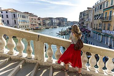 Young woman with red skirt photographed, bridge on the Grand Canal, Rialto Bridge, Venice, Veneto, Italy, Europe
