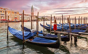 Woman with red dress looking at Venice, evening mood, sunset at the Grand Canal, gondolas at the pier, Campanile bell tower, Venice, Veneto region, Italy, Europe