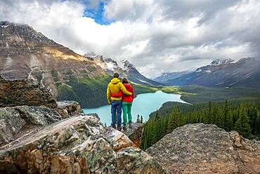 Couple hugging, looking into the distance, view of turquoise glacial lake surrounded by forest, Peyto Lake, Rocky Mountains, Banff National Park, Alberta Province, Canada, North America