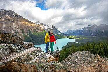 Couple kissing, view of turquoise glacial lake surrounded by forest, Peyto Lake, Rocky Mountains, Banff National Park, Alberta Province, Canada, North America