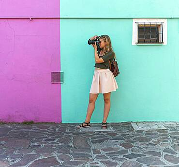 Young woman in front of colorful house, pink and turquoise house facade, tourist photographed on Burano Island, Venice, Veneto, Italy, Europe
