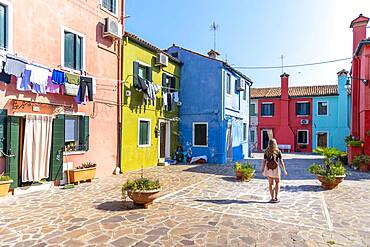 Young woman in front of colorful houses, colorful house facades, Burano Island, Venice, Veneto, Italy, Europe