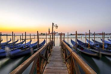 Boat landing stage, jetty with Venetian gondolas, in the back church San Giorgio Maggiore, long exposure, dawn, Venice, Veneto, Italy, Europe
