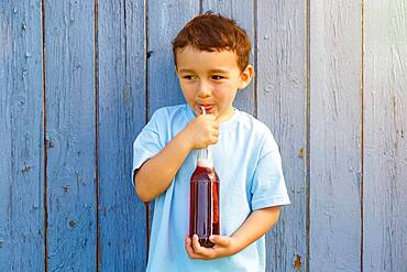 Child little boy drinking cola lemonade drinking bottle, germany