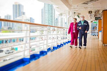 Senior couple walk along passenger cruise ship Ddck wearing face masks, USA, North America