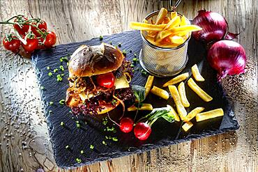 Burger, Swabian Maultaschenburger with fries, served seviert
