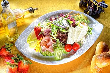 Mixed salad with cheese and ham on plate