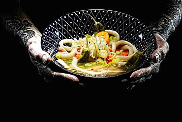 Tattooed hands hold plate with udon bowl, japanese noodle soup